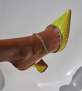 GILDA MULE in lemon hologram glitter features crystal chains and the signature Amina Muaddi flared heel